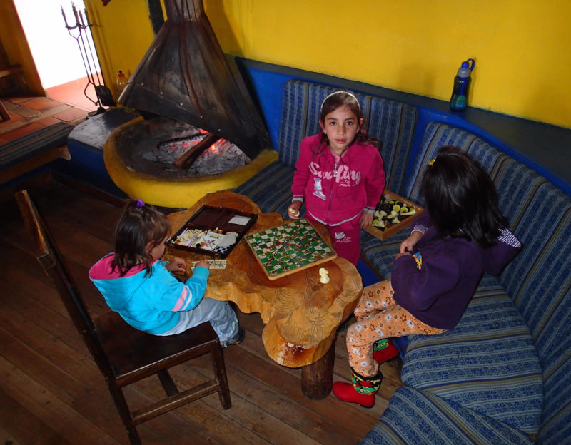 Children play ladder game at the fireplace in Cuello de Luna